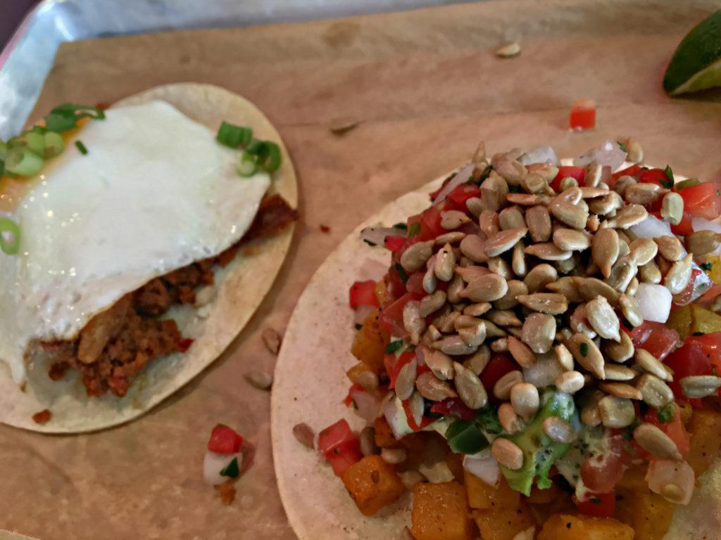 Foreground: Squashacado - roasted butternut squash, fresh avocado, sunflower seeds, cilantro and pico de gallo